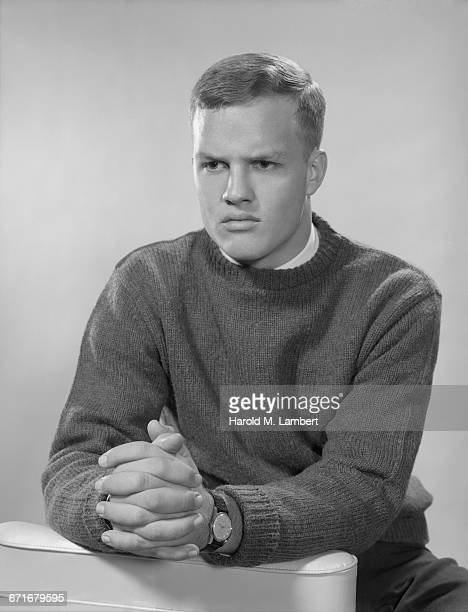 portrait of man with hands clasped and thinking - {{ contactusnotification.cta }} stockfoto's en -beelden