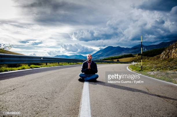 portrait of man with hands clasped sitting on road against sky - cuomo stock pictures, royalty-free photos & images