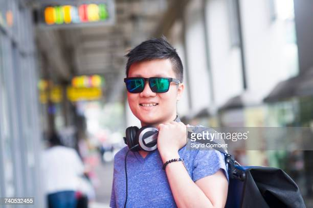 portrait of man with headphone wearing sunglasses looking at camera smiling - sigrid gombert fotografías e imágenes de stock