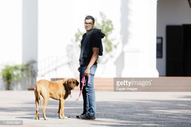 portrait of man with his dog in sunny day by colonial building - bokeh museum stock photos and pictures