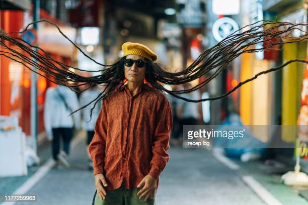 portrait of man with his long dreadlocks flying in air at night - in the center stock pictures, royalty-free photos & images