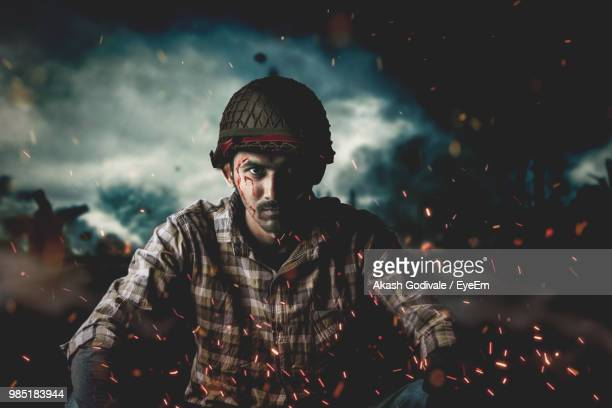 portrait of man with injured face sitting amidst sparks - south asia stock pictures, royalty-free photos & images