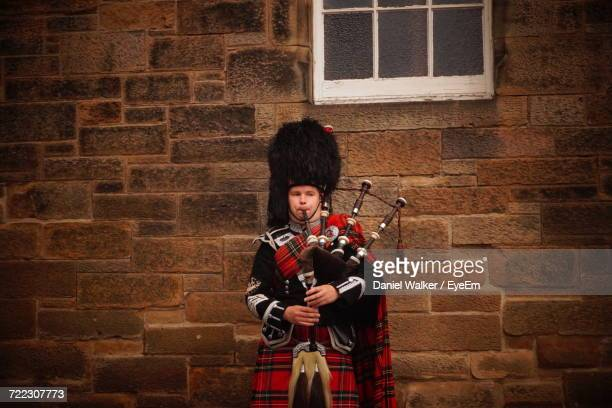 portrait of man with instrument against wall - bagpipes stock pictures, royalty-free photos & images