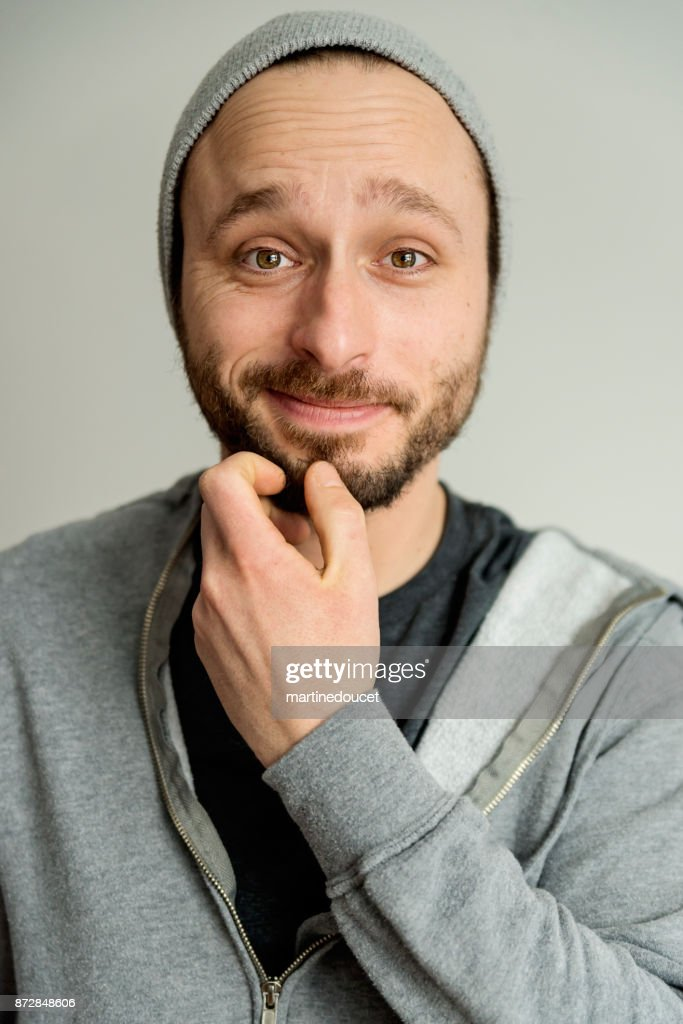 Portrait of man with light beard wearing hat and hoodie. : Stock Photo