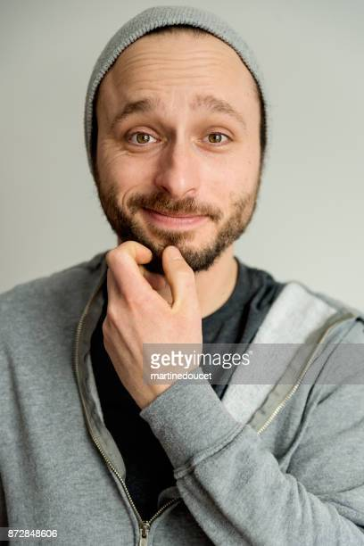 Portrait of man with light beard wearing hat and hoodie.