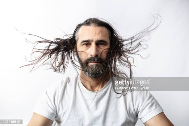 portrait of man with long hair against white background - tousled hair stock pictures, royalty-free photos & images