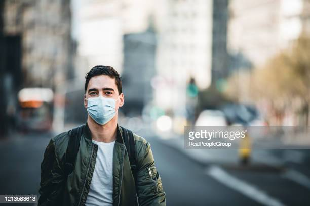 portrait of man with mask on the street. - protective face mask stock pictures, royalty-free photos & images