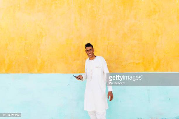 portrait of man with mobile phone wearing tradional clothing standing in front of colourful wall, algeria - algeria stock pictures, royalty-free photos & images