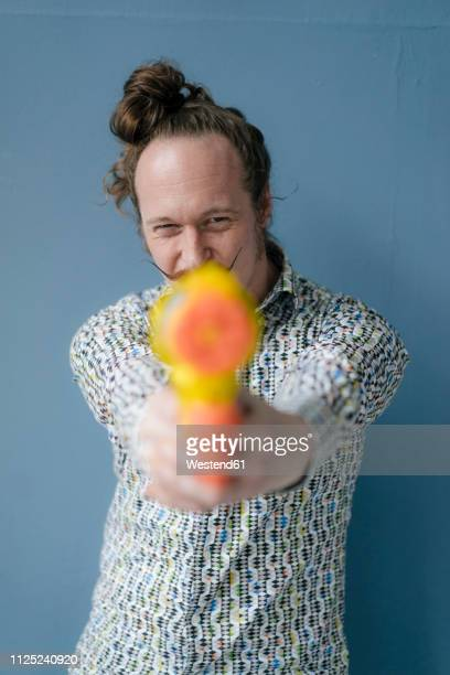 portrait of man with moustache holding water gun at blue wall - man bun stock pictures, royalty-free photos & images