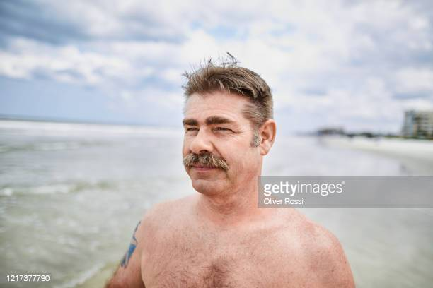 portrait of man with moustache on the beach looking out - schnurrbart stock-fotos und bilder