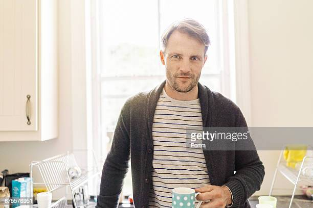 Portrait of man with mug while standing in kitchen