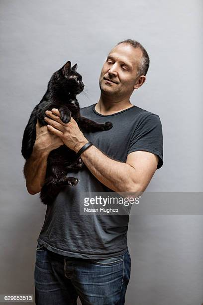 Portrait of man with pet cat on gray background