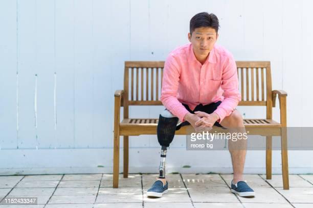 portrait of man with prosthesis leg sitting at bench - homens de idade mediana imagens e fotografias de stock