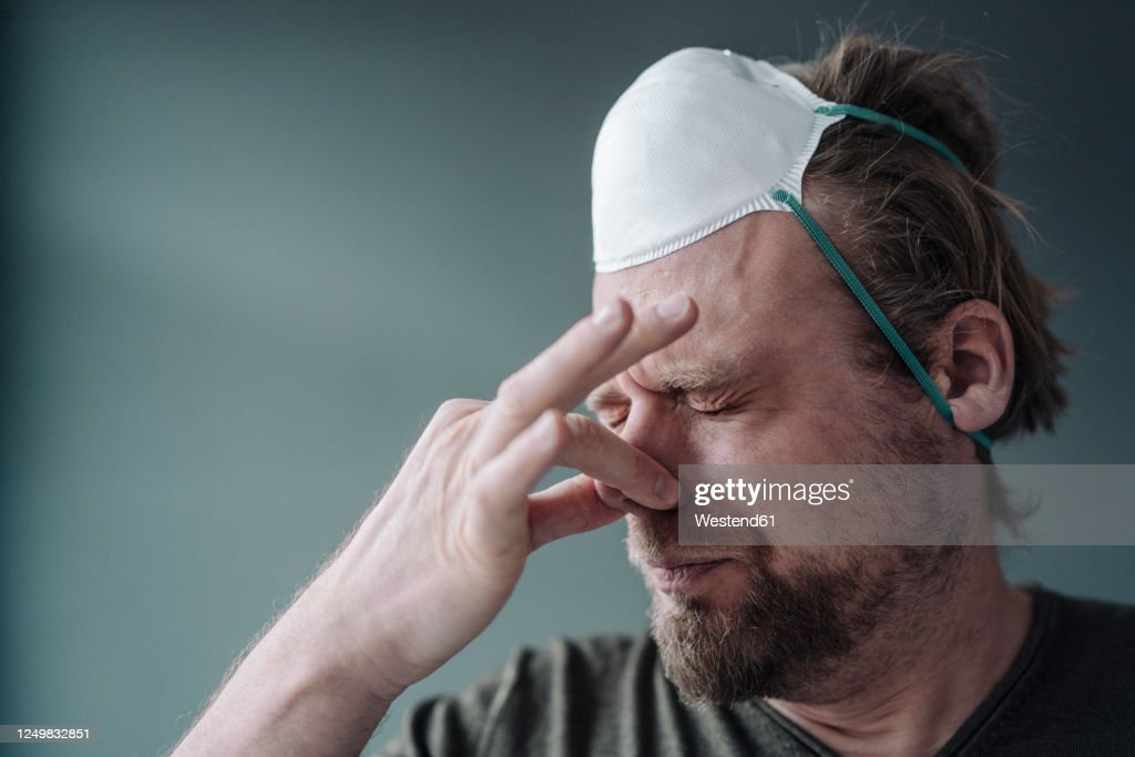 Portrait of man with protective mask holding nose : ストックフォト