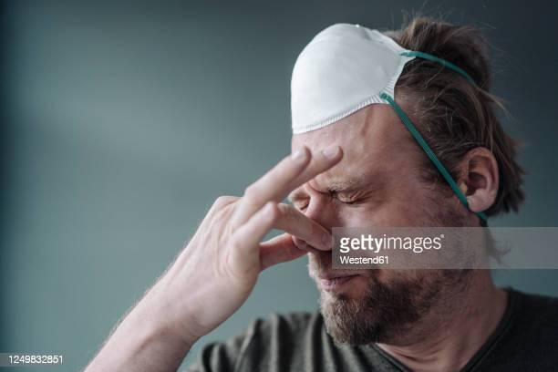 portrait of man with protective mask holding nose - 鼻をつまむ ストックフォトと画像