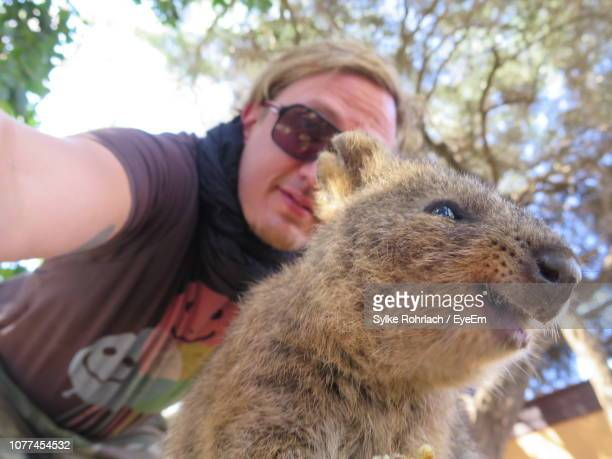 Portrait Of Man With Quokka Against Tree