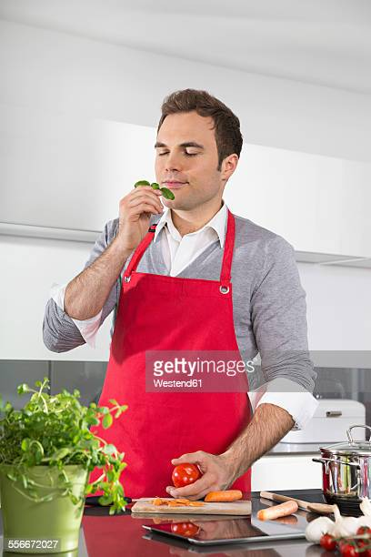 Portrait of man with red apron standing in kitchen smelling basil