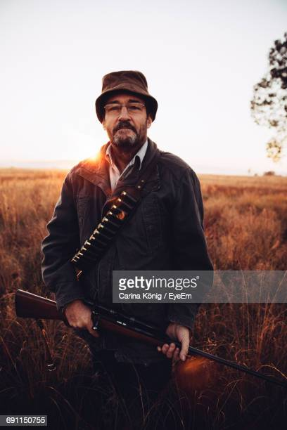 Portrait Of Man With Sniper Standing On Field Against Sky
