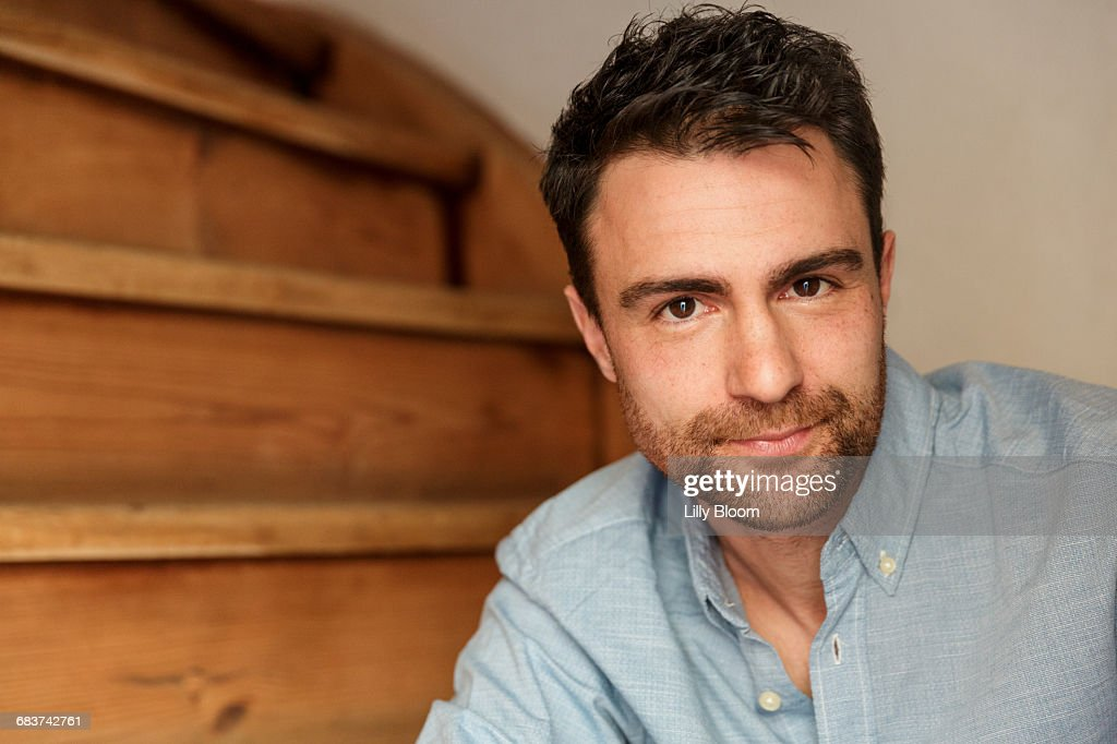 Portrait of man with stubble on stairway looking at camera : Stock-Foto