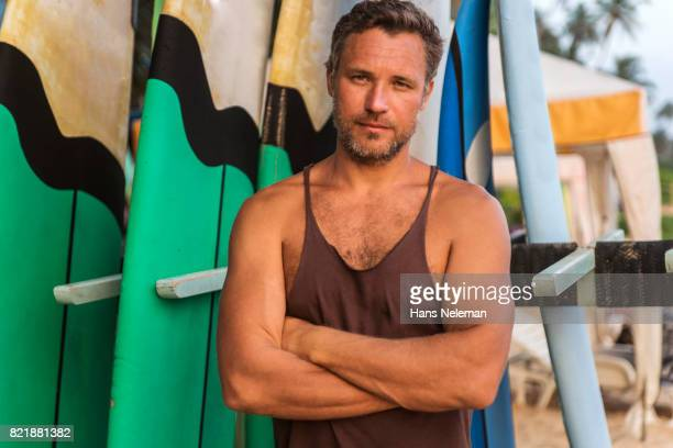 Portrait of man with surfboards on beach
