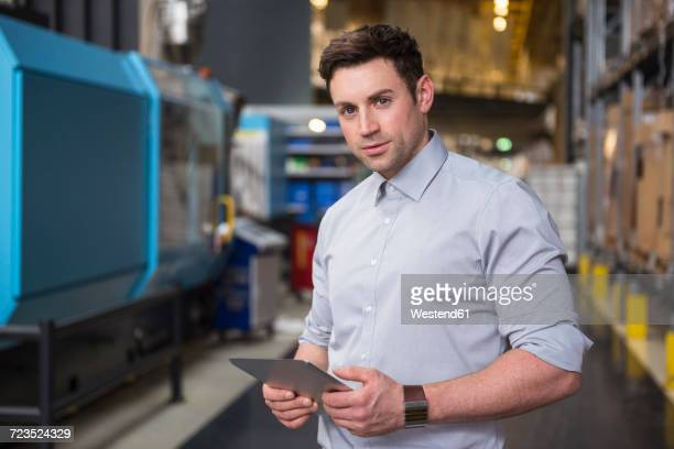 Portrait of man with tablet in factory warehouse