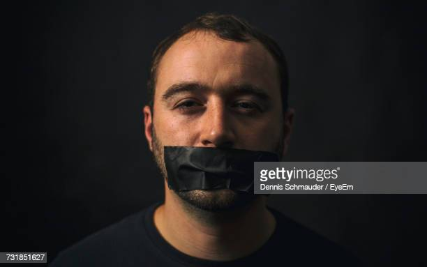 Portrait Of Man With Tape On Mouth Against Black Background