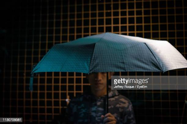 portrait of man with umbrella - jeffrey roque stock photos and pictures