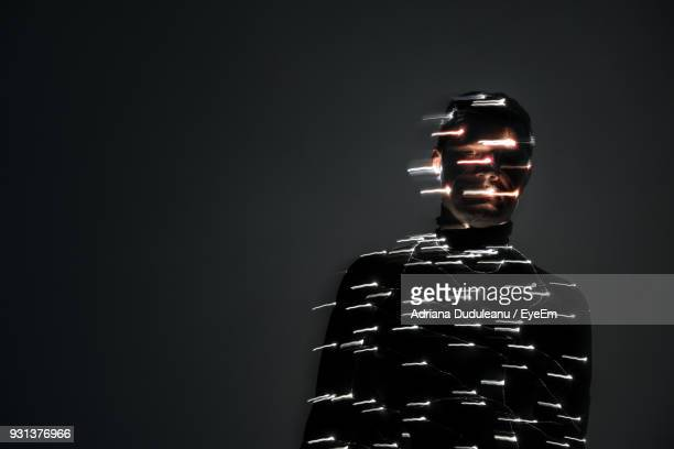 Portrait Of Man Wrapped With Illuminated String Light In Darkroom