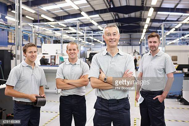 Portrait of manager and workers in engineering factory