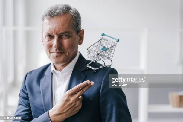 portrait of manager with mini shopping cart - finanzen und wirtschaft stock-fotos und bilder
