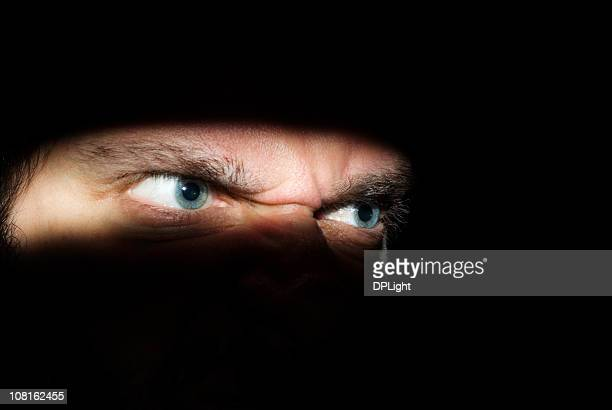 Portrait of Man's Angry Eyes in Shadows