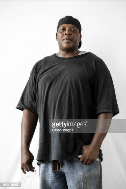 portrait of manual worker standing against white background - fat black man stock photos and pictures