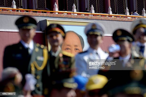 A portrait of Mao Zedong is seen behind a group of Chinese military officers standing in a reviewing stand before a military parade at Tiananmen...