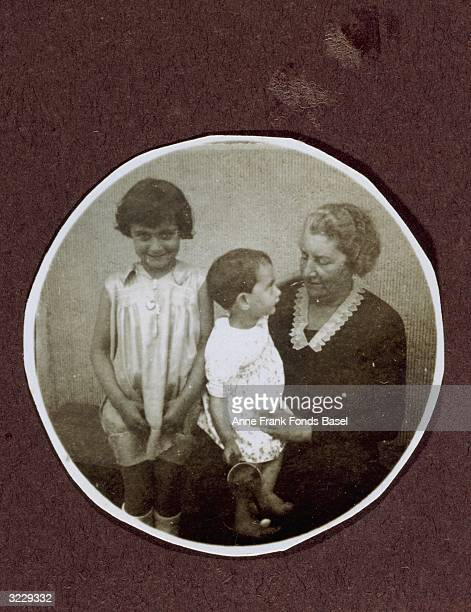 A portrait of Margot Frank standing next to an elderly woman with Anne Frank on her lap A page from Margot Frank's photo album
