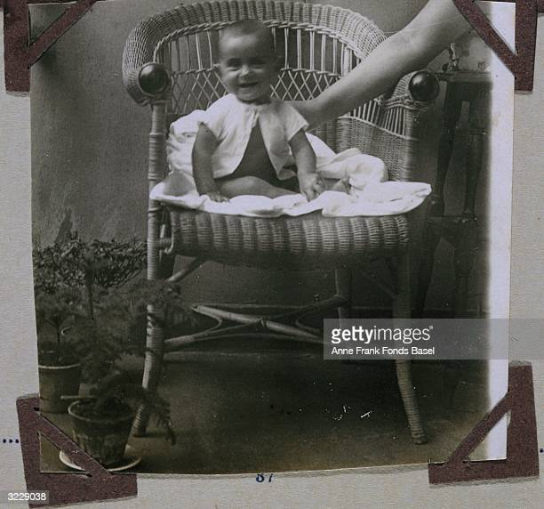 Portrait of Margot Frank the older sister of Anne Frank as an infant sitting in a wicker chair on the balcony of her home taken from her photo album...