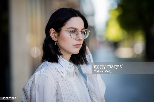 Portrait of Maria Barteczko wearing white striped silk blouse Celine black striped pants Adidas white socks Balenciaga black studded bag Valentino...