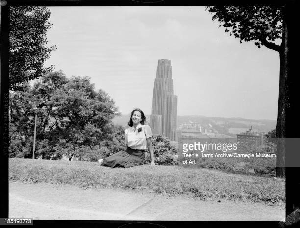 Portrait of Marie Conners wearing dark pleated skirt and trumpet shaped brooch seated on lawn with trees and University of Pittsburgh Cathedral of...