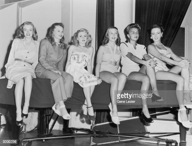 Portrait of Marilyn Monroe sitting on a table next to Joan Caulfield and four other young women at the KFI Camera Clinic