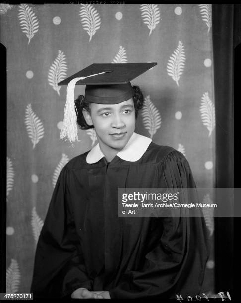 Portrait of Marion Harris wearing dark graduation gown with light colored collar and mortar board posed in front of leaf patterned background in...