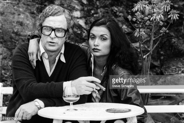 Portrait of married actors Michael Caine and Shakira Caine as they sit on a bench outside their home, Los Angeles, California, 1982.