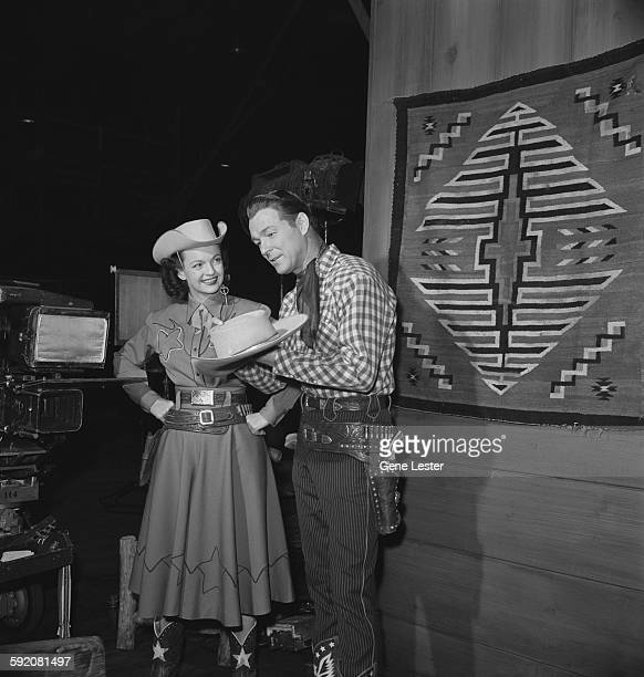 Portrait of married American entertainers Dale Evans and Roy Rogers during the filming of the NBC television program 'Hollywood vs TV' February 2 1952