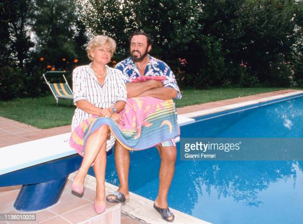 Portrait of married couple Adua Pavarotti and Italian tenor Luciano Pavarotti as they sit on a diving board at their home, Pesaro, Italy, 1993.