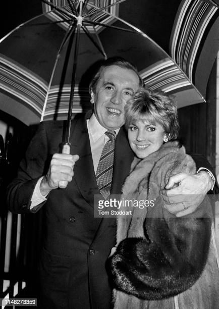 Portrait of married couple British broadcast journalist Sir David Frost and actress Lynne Frederick as they stand under an umbrella London England...