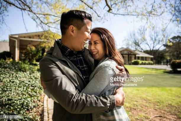 portrait of married couple embracing in front of home - mortgage stock pictures, royalty-free photos & images