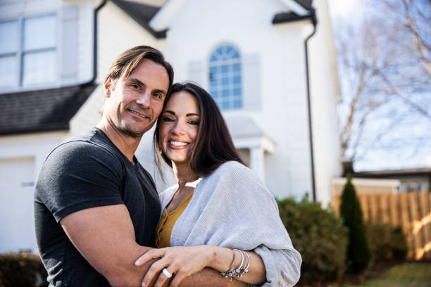 Portrait of married couple in front of new home