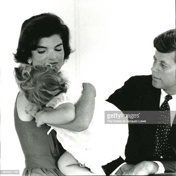 Portrait of married couple Jacqueline Kennedy and Senator John F Kennedy as they pose with their daughter Caroline Hyannis Port Massachusetts Summer...