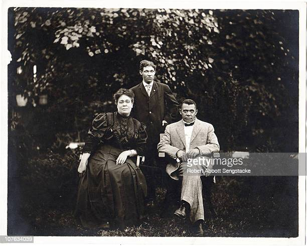 Seated portrait of Booker T Washington and his wife Margaret Murray Washington with his son Ernest Davidson Washington standing behind them outdoors...