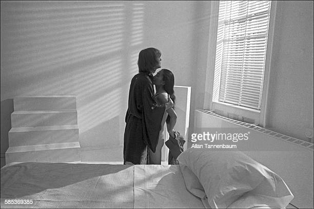 Portrait of married musicians John Lennon and Yoko Ono both dressed in kimonos as they embrace beside a bed in a SoHo gallery New York New York...