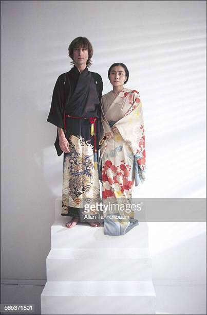 Portrait of married musicians John Lennon and Yoko Ono both dressed in kimonos as they stand on a step in a SoHo gallery New York New York November...