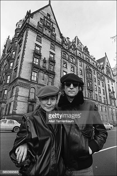 Portrait of married musicians John Lennon and Yoko Ono both in leather jackets and berets as they pose across the street from the Dakota Apartments...